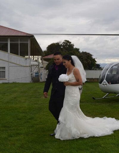 Bride and brother in front of helicopter